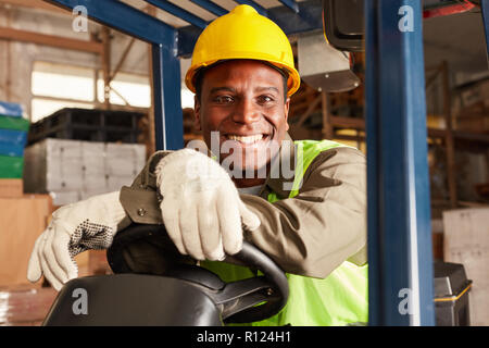 African logistics man as a forklift driver in the warehouse of a freight forwarder - Stock Photo