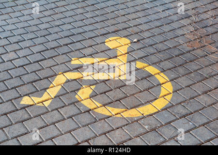 Post with disabled parking space and sign in front of parking bay in car park / Marked parking for people with special needs / Handicapped symbol. - Stock Photo