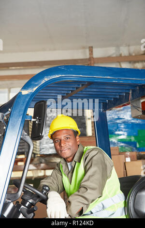 African man on the forklift works as a driver in the warehouse - Stock Photo