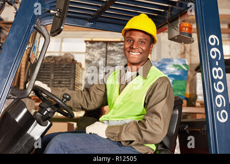 African man as a forklift driver in training in the logistics center - Stock Photo
