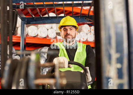Worker as forklift driver on the forklift in the forwarding warehouse - Stock Photo
