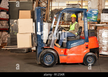 Worker transports delivery with forklift in shipping center - Stock Photo