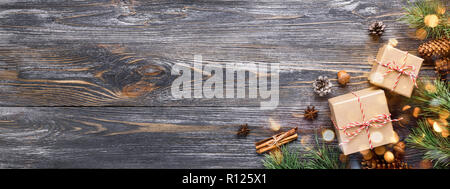 Christmas gifts. Two gift boxes with cinnamon sticks, pine cones, anise stars and pine branches on wooden table with garland lights bokeh. Top view, banner for website. - Stock Photo