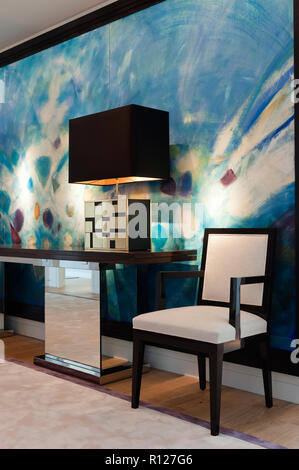 Chair and lamp in front of modern painting - Stock Photo