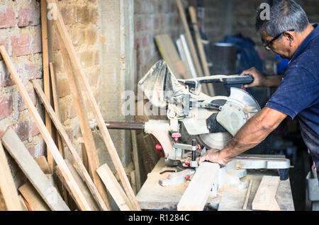Circular saw for cutting boards into the hands of the professional carpenter, construction and home renovation, repair and construction tool - Stock Photo