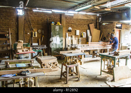Man doing woodwork in carpentry. Carpentry workshop. Carpenter working on wood plank in workshop. - Stock Photo