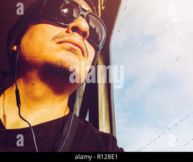 Man in a bus. Handsome young Peruvian man wearing sunglasses looking through bus window. A man sitting on the bus and looks out the window. - Stock Photo