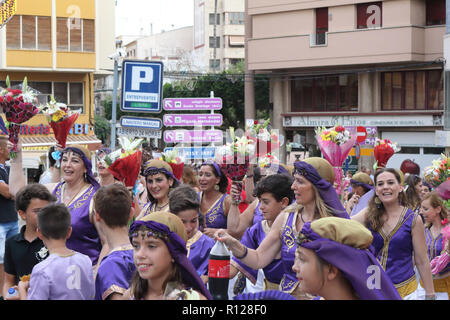 The Moros Almohabenos company women with flowers on a street parade during the Moors and Christians historical reenactment in Orihuela, Spain - Stock Photo