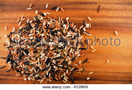 Acacia wood background with medley of aromatic rices. Rice variety includes CalMati Brown Rice, Wild Rice, Sweet Brown Rice & Heirloom Red Rice. - Stock Photo