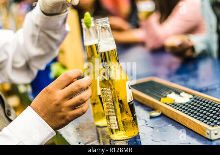 Lima, Peru - October 5th 2018: The waiter uncovers the ice cold beer for the guests at a midday party. - Stock Photo