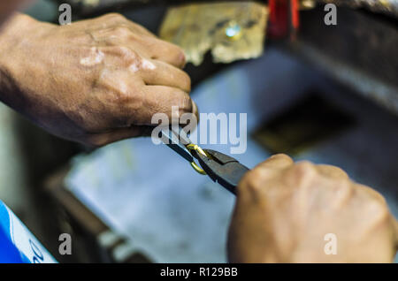 Hands of a jeweler working on a gold ring with a pliers - Stock Photo