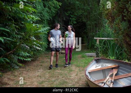 Man and woman carrying yoga mats strolling through garden - Stock Photo