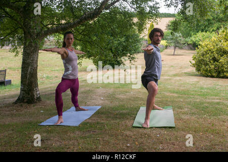 Man and woman doing yoga in garden, practicing warrior pose - Stock Photo