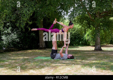 Young man practicing yoga in garden, lying on back balancing woman on feet - Stock Photo