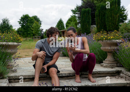 Man and woman practicing yoga in garden, looking at smartphones on patio - Stock Photo
