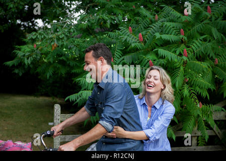 Mature woman riding pillion on bicycle on rural road - Stock Photo