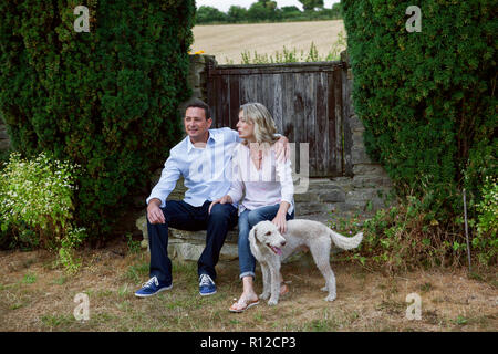 Romantic mature couple with dog sitting in garden - Stock Photo