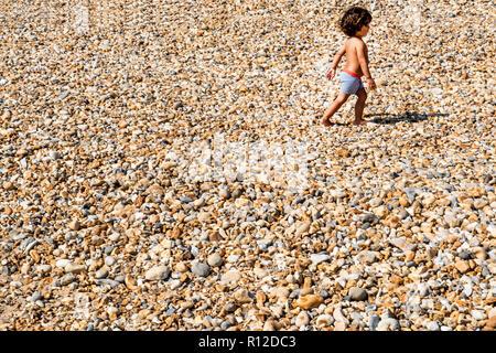 Toddler walking on pebble beach - Stock Photo