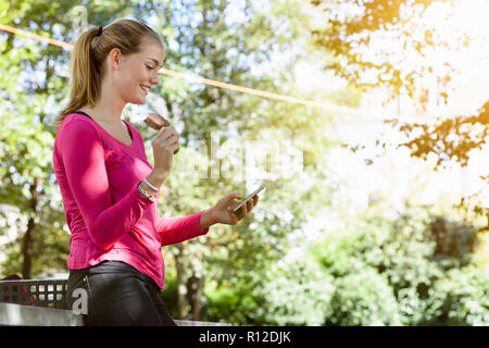 Young woman using smartphone in park - Stock Photo