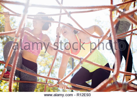 Friends rope climbing in park - Stock Photo