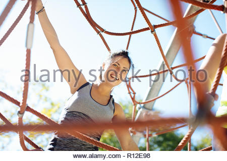 Woman rope climbing in park - Stock Photo