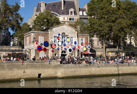 PARIS, FRANCE, SEPTEMBER 8, 2018 - People sit along the shores of the river Seine in a sunny day in Paris, France - Stock Photo