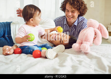 Happy family playing with the baby in the room. Young mother and