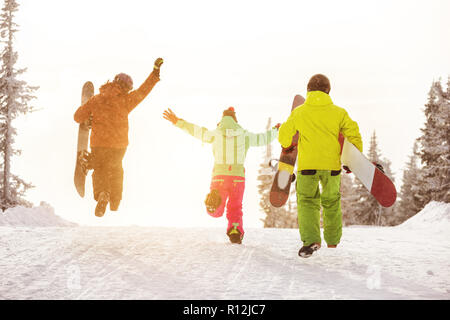 Group of three happy friends snowboarders are having fun and runs to ski slope with snowboards - Stock Photo