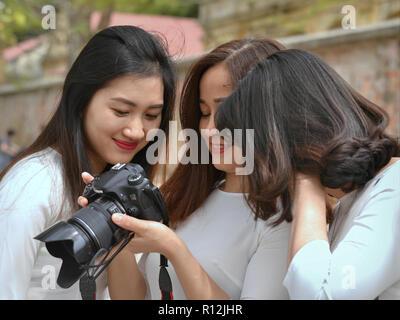 Three young Vietnamese women check photos on the screen of a Canon EOS 70D DSLR camera. - Stock Photo