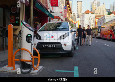 A battery-powered car of car-sharing company blueSG, at a charging station in Mosque Street, Chinatown, Singapore - Stock Photo
