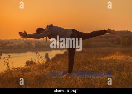 Man doing yoga on sunset with city view,Virabhadrasana III /Warrior Pose III . - Stock Photo