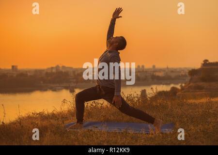Man doing yoga on sunset with city view, Warrior 1 Pose/Virabhadrasana I - Stock Photo