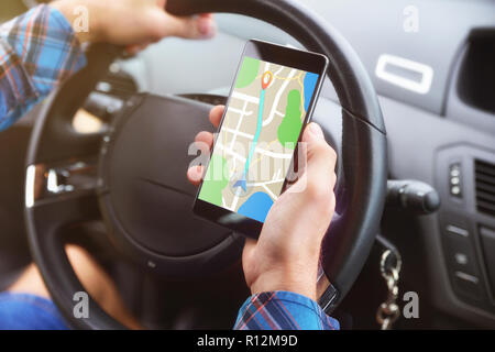 Man consulting a route on a cell phone with an application to reach his destination in a car. - Stock Photo