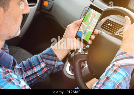 Man consulting a route on a cell phone with an application to reach his destination in a car. Elevated rear view - Stock Photo
