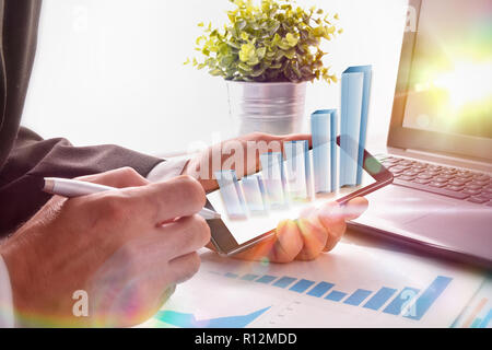 Virtual graphic representation on mobile in the hands of a businessman at the table in an office. Success concept in a business. - Stock Photo