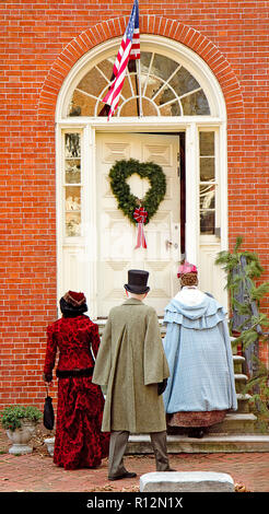 Exterior doors in historic town decorated for the Christmas holidays giving a feeling of yesteryear.  Closeup of doors only. - Stock Photo