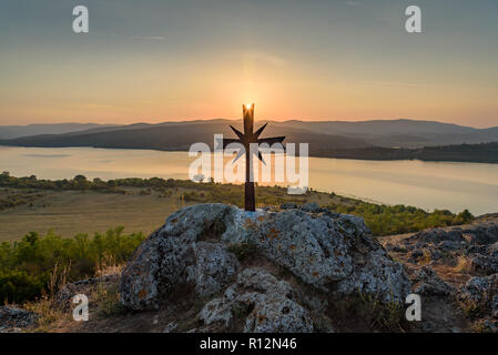 Small stone chapel on a hill top under the last rays of the setting sun - beautiful image, portraying the power of faith in orthodox religion - Stock Photo
