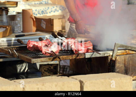 Appetizing delicious fried pieces of meat on skewers are roasted on a large grill in the open air. The chef prepares a barbecue. - Stock Photo