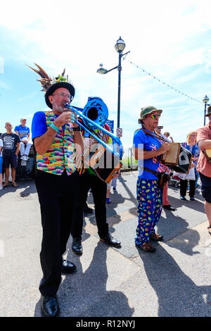 Broadstairs Folk week festival. Senior male wearing hat with feathers, Folk musician, standing outdoors with others, while playing a blue trombone. - Stock Photo