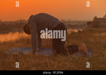 Man doing yoga on sunset with city view,Marjaryasana/Cat pose.Toned image. - Stock Photo