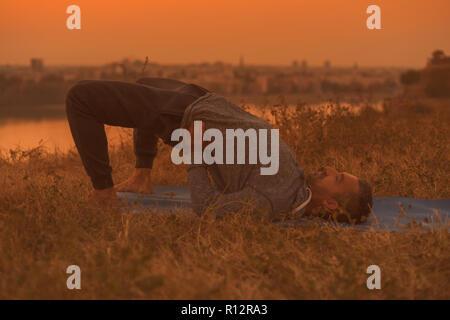 Man doing yoga on sunset with city view, Setu Bandha Sarvangasana/Supported Bridge Pose - Stock Photo