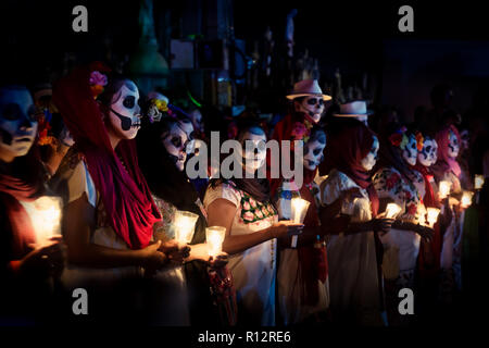 Merida, Cementerio General, Mexico - 31 October 2018: Line of customed women dressed as Catrinas with skull make-up and candles at the event for dia d - Stock Photo