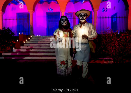 Merida, Cementerio General, Mexico - 31 October 2018: Customed man and woman with with mexican traditional white clothes and skull make-up in front of - Stock Photo