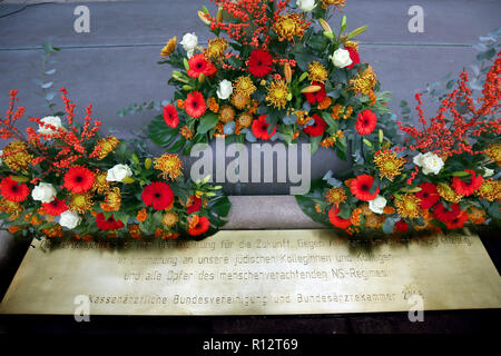 Berlin, Germany. 08th Nov, 2018. Flowers and a commemorative plaque can be seen in front of the Federal Association of Statutory Health Insurance Physicians at the beginning of a memorial service of the German medical profession to commemorate the persecution of Jewish doctors under National Socialism. 80 years ago, on 30 September 1938, Jewish doctors were deprived of their licences to practise medicine. Credit: Wolfgang Kumm/dpa/Alamy Live News - Stock Photo
