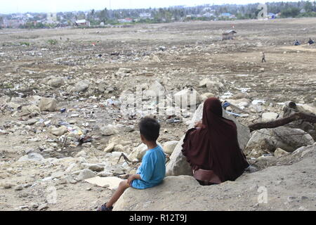A women and kid are seen seated at the site where the earthquake happened. A deadly earthquake measuring 7.5 magnitude and a tsunami wave destroyed the city of Palu and much of the area in Central Sulawesi. The death toll was 2088, around 5000 people were seriously injured and some 62,000 people were displaced. - Stock Photo