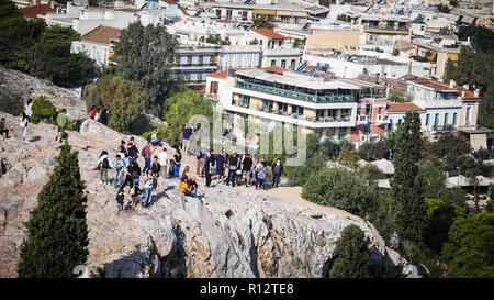 October 24, 2018 - Athens, Attiki, Greece - Tourists seen standing on a rock at the Acropolis Hill..The Acropolis of Athens is an ancient citadel located on a rocky outcrop above the city of Athens and contains the remains of several ancient buildings of great architectural and historic significance, the most famous being the Parthenon. (Credit Image: © Ioannis Alexopoulos/SOPA Images via ZUMA Wire) - Stock Photo