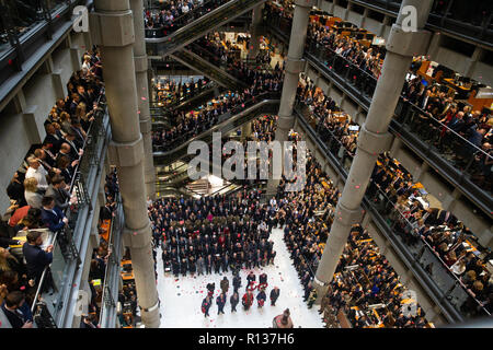 London, UK. 9th Nov 2018. Thousands line the atrium and escalators at Lloyd's commemoration service. Poppy petals fall from above in the atriium as the bugle plays 'The Last Post' . The Lutine Bell sounds during the wreath-laying ceremony with dignitaries including The Lord Mayor of London and Chelsea pensioners with the 7 rifles making up the Guard of honour Credit: Tommy London/Alamy Live News - Stock Photo
