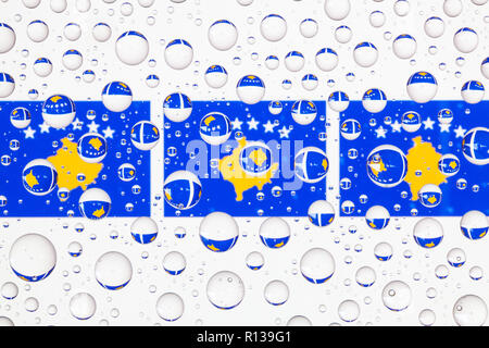 Flags  of Kosovo behind a glass covered with raindrops. 3D illustration - Stock Photo