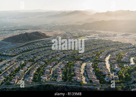 Late afternoon aerial view towards new suburban homes and streets in the sprawling Porter Ranch neighborhood of Los Angeles, California.  The Santa Su - Stock Photo