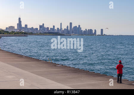View of Chicago skyline with person wearing red in foreground, shot at Lake Michigan waterfront, just north of Oakwood-41st St. Beach on South Side. - Stock Photo